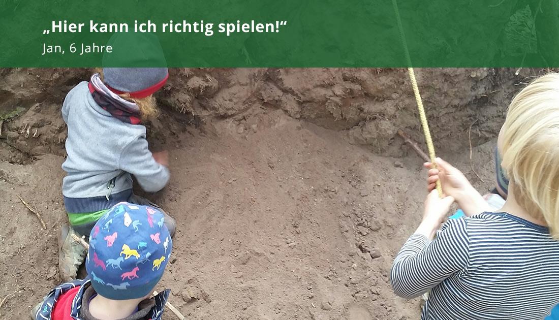 Kinder mit Stöckern im Sand
