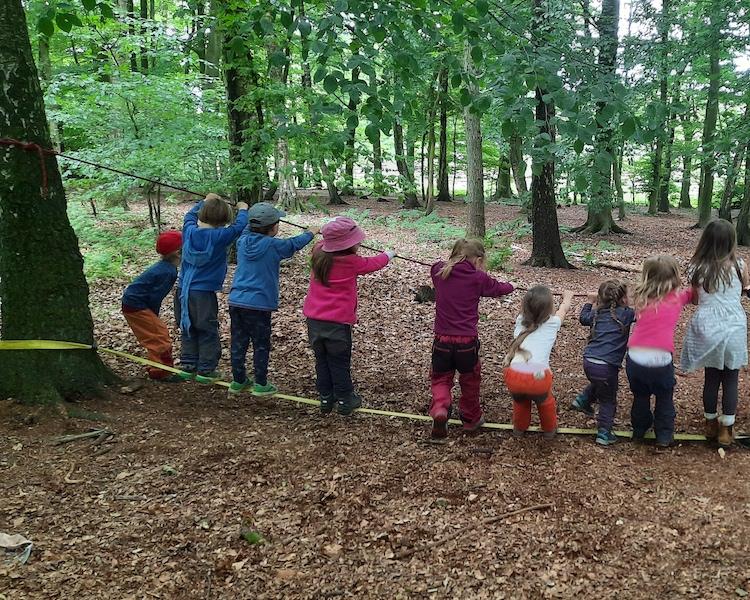 Kinder im Wald auf Slackline