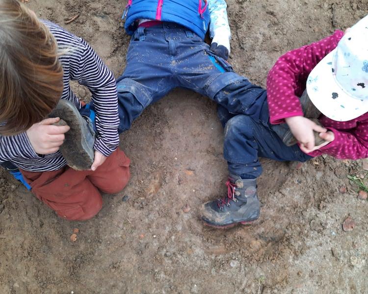 Kinder spielen Pferd, kratzen Hufe aus