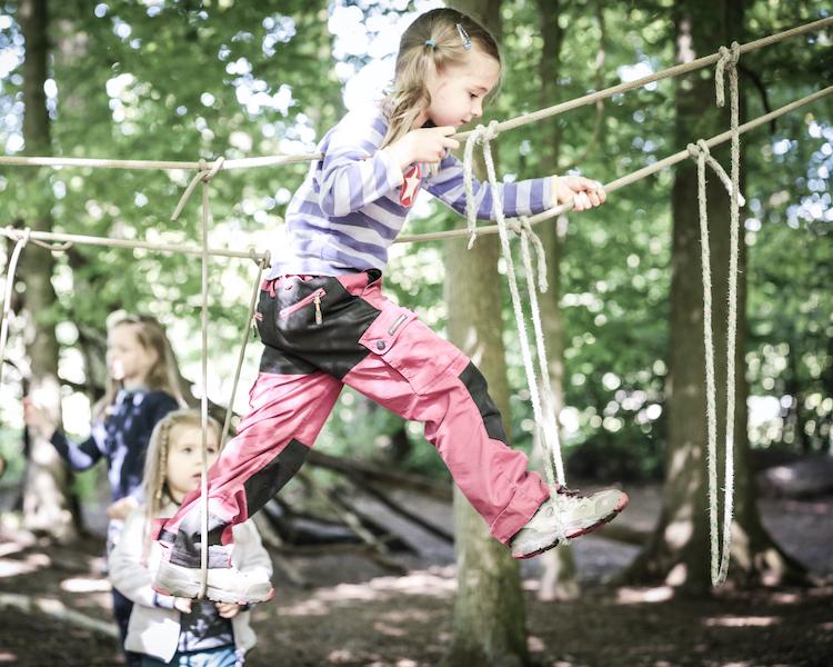 Kind auf Seilbrücke, Konzept, Waldkinder sind stabil